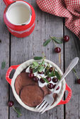 Chocolate pancakes with cocoa, sour cream and fresh sweet cherry — Stock Photo