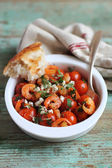 Roasted cherry tomatoes and shrimps with feta cheese and chopped parsley in a baking dish — Stock Photo