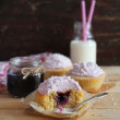 Valentine day cupcakes with blackcurrant jam, pink whipped cream cheese and coconut on a wooden surface — Stock Photo