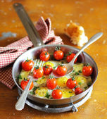 Sunny side up fried quail eggs with roasted cherry tomatoes — Stock Photo