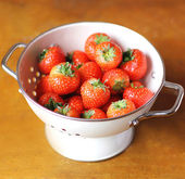 Fresh organic ripe strawberry harvest or crop in a white colander on a rustic wooden table — Stock Photo
