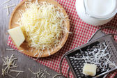 Ingredients for pasta cheese sauce or pizza, freshly grated parmesan or cheddar hard cheese, raw milk in a pot, kitchen tools, grater, wooden plate and kitchen towel, rustic vintage style — Stock Photo