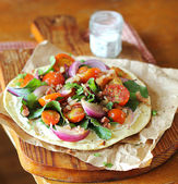 Summer vegetable salad with halved cherry tomatoes, green chard leaves, roasted bacon, violet onion, salt and pepper on a whet flat bread — Stock Photo