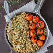 Pie with cod fillet white fish, flax, sunflower seeds, pine nuts, bread crumbs and chopped fresh chives served with roasted cherry tomatoes in a pan — Stock Photo