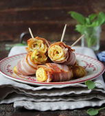 Roasted egg rolls with crispy bacon and spinach leaves on a plate — Foto Stock
