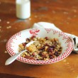 Healthy homemade prganic granola or muesli with oat flakes, dried fruits and nuts in a plate with a bottle of milk for breakfast — Stock Photo