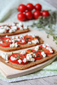 Rye bread bruschetta with sliced cherry tomatoes, crumbled cottage cheese and dried thyme on a wooden board for breakfast or summer picnic snack — Stock Photo