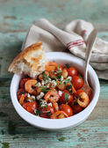 Traditional mediterranean dish with roasted roma tomatoes, garlic prawns, crumbled feta cheese and chopped fresh parsley in a bowl ready for lunch and healthy dinner — Stock Photo