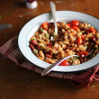 White kidney bean stew with roasted cherry tomatoes, red sweet pepper, sausages, chili and fresh parsley in a plate — Stock Photo #42715667