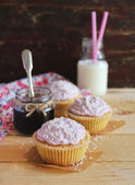 Cupcakes with berry marmalade and buttercream frosting on a wooden table — Stock Photo