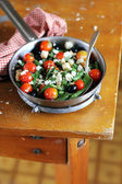 Warm summer salad with roasted cherry tomatoes, blanched french green beans. crumbled feta cheese, clack olives and crispy croutons in a pan for healthy lunch — Stock Photo