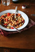 White kidney bean stew with roasted cherry tomatoes, red sweet pepper, sausages, chili and fresh parsley in a plate — Stock Photo