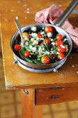 French green bean saute with roasted cherry tomatoes, black olives, crumbled feta cheese and wheat croutons in a pan — Stock Photo