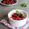 Healthy homemade crumbled cottage cheese with sour cream, honey, vanilla, fresh red and black currants, strawberry and mint leaves in a bowl for breakfast — Stock Photo #44940597