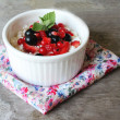 Healthy homemade crumbled cottage cheese with sour cream, honey, vanilla, fresh red and black currants, strawberry and mint leaves in a bowl for breakfast — Stock Photo #44941053