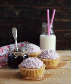 Homemade cupcakes with creamy mascarpone frosting, shredded coconut, berry jam and a bottle of fresh milk for Mother's day breakfast, dessert or for wedding sweet table — Stock Photo
