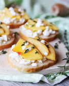 Homemade bruschetta with toasted wheat bread, ripe nectarines and peaches, crumbled feta cheese, dried thyme, honey in a wooden cutting board perfect for summer picnic snack, breakfast, appetizer — Stock Photo