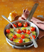 Fried quail eggs with roasted cherry tomatoes, mozzarella cheese, fresh chopped parsley, ground black pepper and a slice of homemade ciabatta in a frying pan for morning breakfast or lunch — Stock Photo
