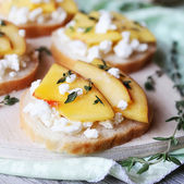 Toasted wheat bread with ripe peaches, crumbled feta or cotatge cheese, honey and thyme for snack or summer picnic — Stock Photo