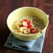 Bowl of oatmeal porridge served with fresh chopped strawberry, banana slices and freshly shredded coconut for morning breakfast or healthy snack, selective focus — Stock Photo