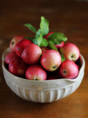Red apples harvest in a white bowl on a wooden table, selective focus — Stock Photo