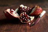 Fresh juicy ripe pomegranate on a wooden table with a knife — Stock Photo