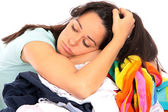 Bored Young Woman Lying on Pile of Clothes — Stock Photo