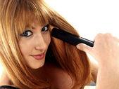 Woman Using Hair Straighteners — Stock Photo