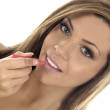 Young Woman Puting On Lip Gloss - Stockfoto