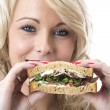 Attractive Young Woman Eating a Sandwich — Stock Photo