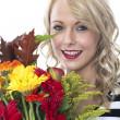 Stock Photo: Attractive Young Woman Holding a Bunch of Flowers