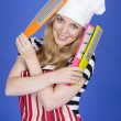 Young Woman in Chefs Hat Holding Kitchen Utensils — Stock Photo #34127293