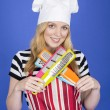Young Woman in Chefs Hat Holding Kitchen Utensils — Stock Photo #34128517