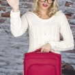 Attractive Young Woman Holding a Suitcase Waving — Stock Photo