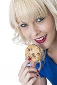 Junge frau, die einen chocolate chip cookie keks essen — Stockfoto