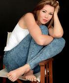 красивая молодая женщина, сидя в кресле — Стоковое фото
