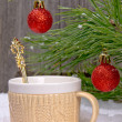 Mug in the snow on a background decorated with pine branches — Stock Photo