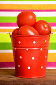 Red tomatoes in a bucket — Stock fotografie