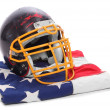 Old scratched football helmet on a american flag. — Stock Photo