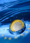 Euro coin falling to the water. — Stock Photo