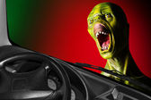 Screaming zombie and speedy car. — Stock Photo