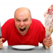 Angry hungry man (boss) with knife and raw bloody meat. Downsizing metaphor — Stock Photo #29590365