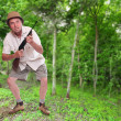 Постер, плакат: Funny picture of a crazy hunter with his hunting rifle in a tropical forest