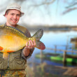 The fisherman with his big Carp at a beautiful lake in The South Bohemia. Czech Republic, Europe. — Stock Photo #29592063