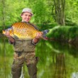 Stock Photo: The fisherman with his big carp at a beautiful river.