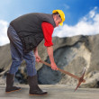 Working man with pick axe in a coal mine. Under construction concept. — Stock Photo #29592147