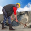 Stock Photo: Working mwith pick axe in coal mine. Under construction concept.