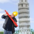 Stock Photo: Funny picture of worried builder using a spirit level against leaning tower of Pisa.