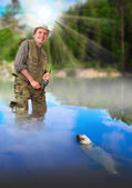 The fisherman catching a fish on a wild river in rural landscape. — Stock Photo