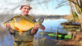 The fisherman with his big Carp at a beautiful lake in The South Bohemia. Czech Republic, Europe. — Stock Photo